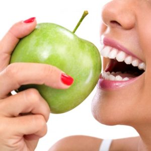 closeup-of-the-face-of-a-woman-eating-a-green-apple-s-580x580